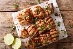 Afghanistan`s barbecue: grilled chicken skewers Kebab e Murgh cl. Ose-up on paper on a table. horizontal top view from above stock images