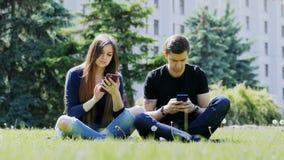 Afhankelijk van de telefoonmensen die de telefoon in het park, de ernstige verslaving van de celtelefoon gebruiken stock video