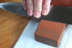 Afiando a faca do cozinheiro chefe Fotografia de Stock Royalty Free