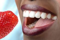 afican妇女的完善的牙用草莓 库存图片