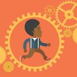 Afican man running inside a gear Stock Image