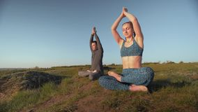 Afición de la yoga, par atlético junto en el pico de montaña que medita en la posición de loto respecto al fondo del cielo almacen de metraje de vídeo