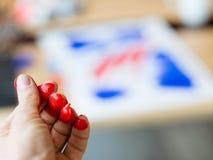 Afici?n roja de la pintura de la creatividad de los fingeres de la pintura del artista fotos de archivo