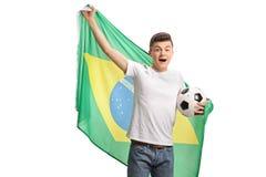 Aficionado al fútbol adolescente alegre que sostiene un fútbol y un fla brasileño Fotografía de archivo