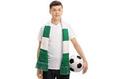 Aficionado al fútbol adolescente con una bufanda y un fútbol Fotografía de archivo libre de regalías