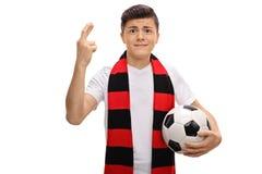 Aficionado al fútbol adolescente con una bufanda y un fútbol que llevan a cabo su finge Fotos de archivo libres de regalías