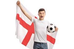 Aficionado al fútbol adolescente emocionado con una bandera inglesa y un fútbol Imagen de archivo