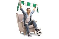 Aficionado al fútbol adolescente extático con una bufanda y una sentada del fútbol Imágenes de archivo libres de regalías