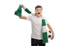 Aficionado al fútbol adolescente extático con una bufanda y un fútbol Imagenes de archivo