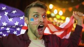 Aficionado al fútbol americano extremadamente feliz que agita la bandera nacional, celebrando meta, triunfo almacen de metraje de vídeo