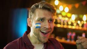 Aficionado al fútbol con la bandera argentina pintada en la competencia que gana del equipo feliz de la mejilla almacen de metraje de vídeo