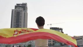 Aficionado al fútbol de la chica joven que sostiene una bandera de España en la ciudad, fps del concepto 50 del campeonato almacen de metraje de vídeo