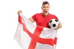 Aficionado al fútbol emocionado que sostiene un fútbol y una bandera inglesa Imagen de archivo