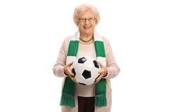 Aficionado al fútbol mayor encantado con una bufanda y un fútbol Foto de archivo libre de regalías