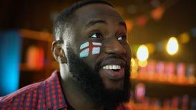 Aficionado al fútbol negro alegre con la bandera inglesa pintada en la mejilla que celebra la victoria almacen de video