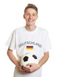 Aficionado al fútbol alemán de risa con el pelo rubio y la bola Foto de archivo libre de regalías
