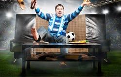 Aficionado al fútbol en el sofá Imágenes de archivo libres de regalías
