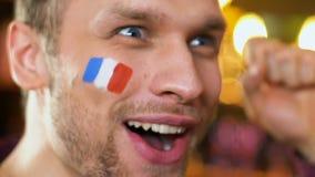 Aficionado deportivo francés extremadamente feliz sobre el juego que gana del equipo preferido, bandera en mejilla almacen de metraje de vídeo