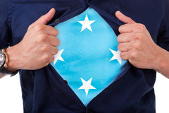 Aficionado deportivo joven que abre camisa y que muestra a la bandera su cuenta Imagenes de archivo