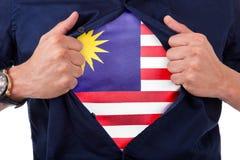 Aficionado deportivo joven que abre camisa y que muestra a la bandera su cuenta Foto de archivo libre de regalías