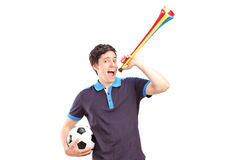 Aficionado deportivo masculino que sostiene un fútbol y un cuerno Foto de archivo libre de regalías