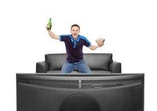 Aficionado desportivo com cerveja e pipoca em suas mãos Foto de Stock