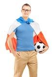 Aficionado desportivo novo com a bandeira da Holanda que guardara uma bola de futebol Foto de Stock