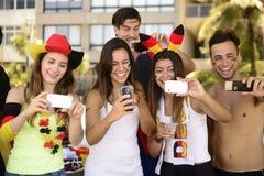 Aficionados al fútbol alemanes que sostienen smartphones imagen de archivo libre de regalías