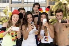Aficionados al fútbol alemanes que sostienen smartphones Imagen de archivo