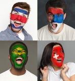 Aficionados al fútbol emocionales con las banderas pintadas en caras imágenes de archivo libres de regalías