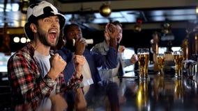 Aficionados al fútbol extremadamente felices que miran el juego en el pub, celebrando meta que anota fotografía de archivo