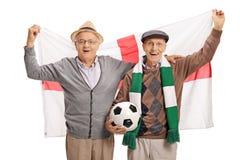 Aficionados al fútbol mayores emocionados con una bandera inglesa Foto de archivo