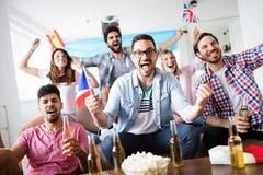 Aficionados al fútbol que miran emocionalmente el juego en la sala de estar Imagenes de archivo