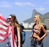 Aficionados deportivos de las mujeres que sostienen la bandera de los E.E.U.U. en Rio de Janeiro con Cristo el redentor en fondo. Imágenes de archivo libres de regalías