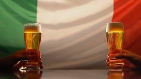 Aficionados deportivos masculinos que sostienen los vidrios de cerveza en el pub, bandera italiana en el fondo, MES lento metrajes