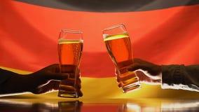 Aficionados deportivos masculinos que tintinean los vidrios de cerveza en el pub, bandera alemana en el fondo, día de fiesta almacen de metraje de vídeo