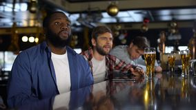 Aficionados deportivos multirraciales que miran el torneo en el pub, decepcionado con el juego perdidoso almacen de metraje de vídeo