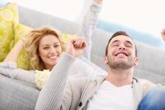 Aficionados deportivos que animan en casa mientras que ve la TV Foto de archivo
