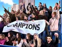 Aficionados deportivos que sostienen la bandera del campeón en tribunas Imagenes de archivo