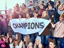 Aficionados deportivos que sostienen la bandera del campeón en tribunas Fotos de archivo libres de regalías
