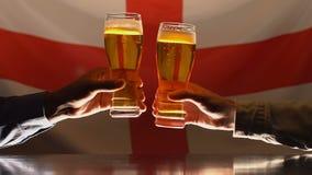 Aficionados deportivos que tintinean los vidrios de cerveza, equipo de apoyo, bandera inglesa en fondo almacen de video