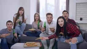 Aficionados desportivos que olham o momento decisivo do jogo e feliz para a vitória que senta-se no sofá na frente da tevê que co vídeos de arquivo
