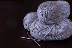 Aficiones y concepto creativo de las actividades - tres madejas de hilado gris con las agujas que hacen punto de la circular del  imágenes de archivo libres de regalías