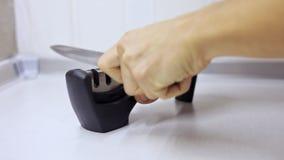 Afiladura de un cuchillo en sacapuntas especiales en una cocina, manos del manual del hombre en primer metrajes