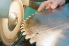 Afilando la circular vio, trabajador afila una hoja de sierra circular fotos de archivo