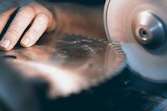 Afilando la circular vio, trabajador afila una hoja de sierra circular foto de archivo libre de regalías