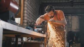 Afilando las herramientas del hierro con las chispas - forje el taller imagen de archivo libre de regalías