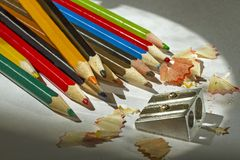 Afilando los lápices multicolores las virutas se cierran para arriba imagen de archivo