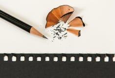 Afile el lápiz en el escritorio blanco Con el papel negro imagenes de archivo