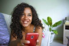 Afilia??o ?tnica misturada bonita e feliz nova caucasiano e mulher afro-americana preta que encontra-se em casa sof? usando o app imagens de stock